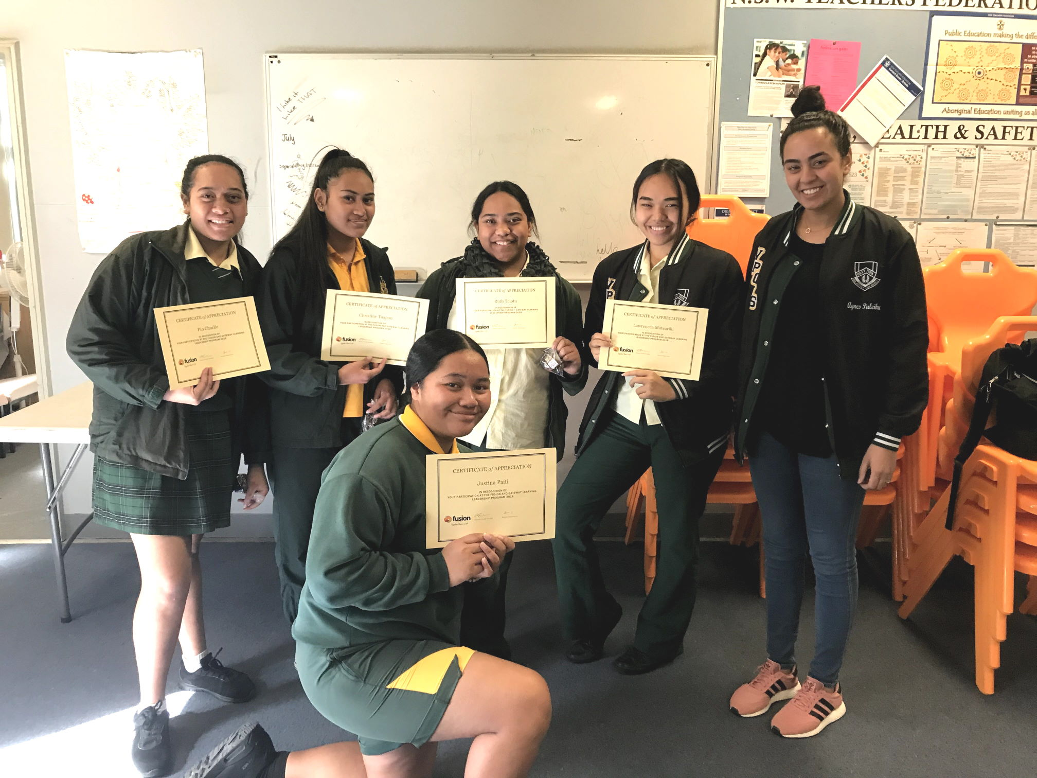 Students hold their certificates of appreciation