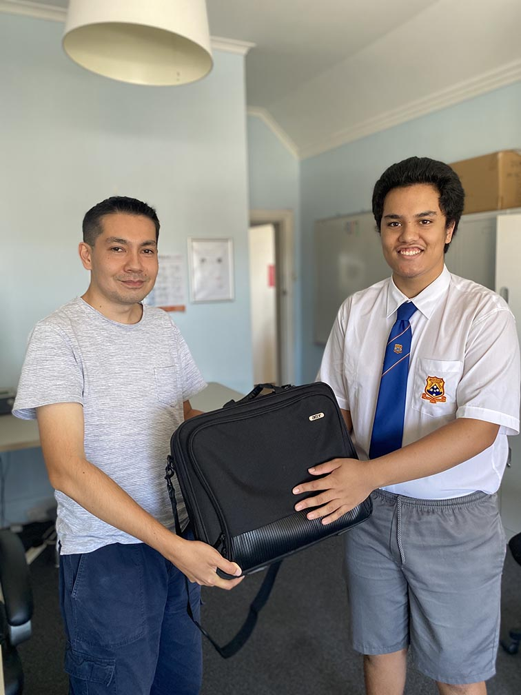 Student being handed a laptop